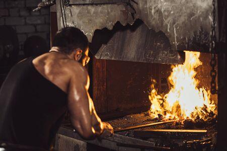jeune forgeron caucasien fort travaillant avec un feu ouvert dans un four. Le forgeron forgeant le fer chaud dans l'atelier
