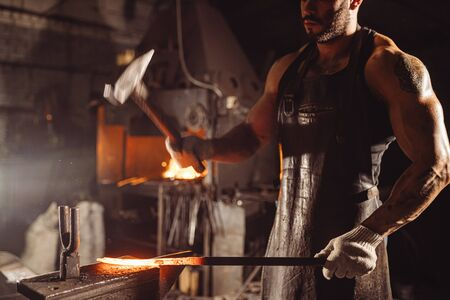 blacksmith beat hot metal with hammer isolated in dark workshop space, wearing leather brown apron and having muscular body