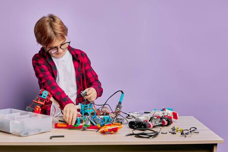 little caucasian kid boy interested in assembling different robots in engineering club isolated over purple background, pats of robot on table
