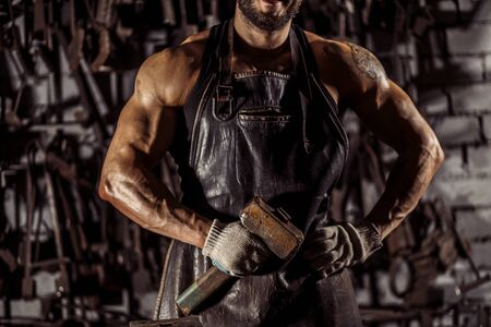 cropped man with muscular body, young forger hold hammer in hands, have beard. instruments in the background Reklamní fotografie