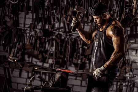 muscular man work at workshop using hammer, wearing leather uniform and having strong body