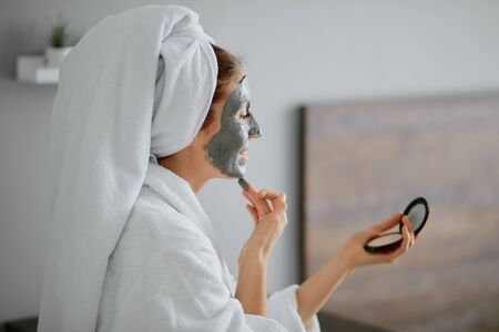 beautiful woman in bathrobe and towel apply facial mask, doing beauty procedures at home, healthcare Zdjęcie Seryjne