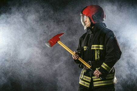 young firefighter preparing to save, to extinguish fire and save people if necessary, holding hammer in hands and wearing protective suit uniform Foto de archivo - 135226734