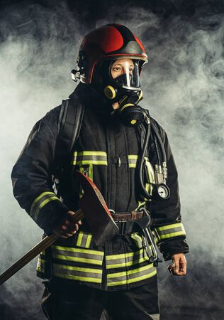 strong middle-aged fireman going to save and protect people from fire, wearing special mask or helmet, protective uniform