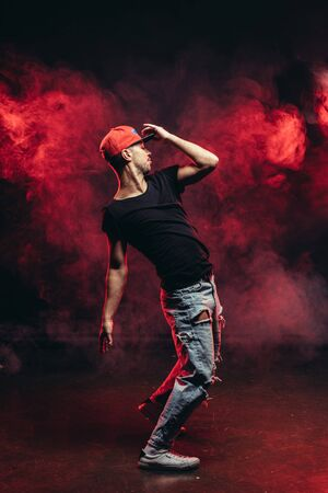young vigorous male dancing isolated over red smoky space, wearing casual wear. street dance concept