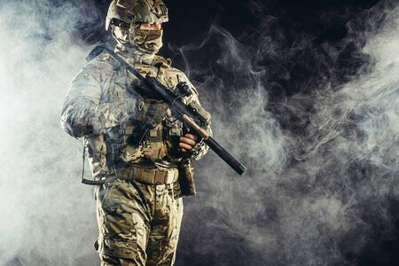military, army, soldiers concept. brave young soldier prepare to attack holding gun in white foggy space