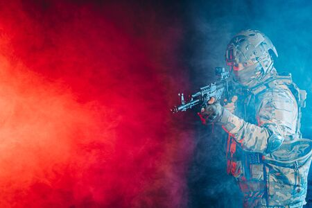 safety and protection concept. young man work as military man protecting country, wearing military forces clothes and holding gun in smoky UV space Фото со стока