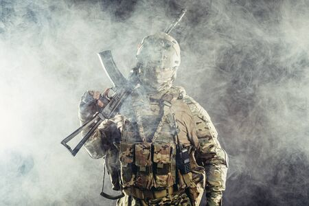 portrait of young army soldier in action with gun, dark and foggy background Banco de Imagens