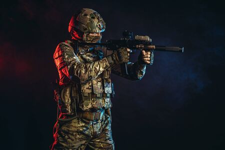 safety and protection concept. young man work as military man protecting country, wearing military forces clothes and holding gun in smoky UV space Standard-Bild