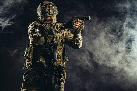 Soldat der Spezialeinheiten, der Maschinengewehr und militärische Ausrüstung im verrauchten Raum hält