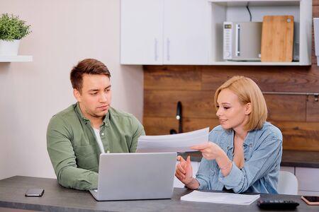 coppia che controlla analizzando le bollette delle utenze seduti insieme al tavolo della cucina, marito e bella moglie che leggono documenti di prestito bancario con il laptop, famiglia che gestisce le finanze pianificando le spese insieme