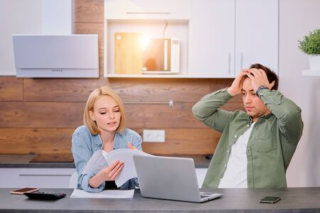 couple using modern laptop computer, looking worried and sad, studying online, solving financial problems at home, anxious, searching for job, reading bad news, searching, talking, using papers Standard-Bild