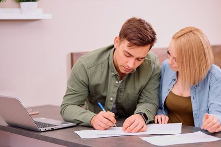 married caucasian couple make notes, going to buy new house or take mortgage, using laptop, planning finance at home Stockfoto
