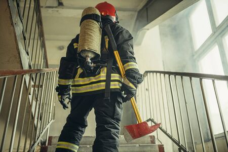 young caucasian fireman holding hammer, risking his life to save people from fire, wearing protective uniform