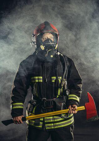 Fuerte bombero seguro que salva y protege del fuego, usa casco y traje protector, trabaja en la estación de bomberos