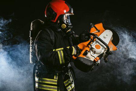 junger Feuerwehrmann, der einen Kettensägenstand isoliert über rauchigem Hintergrund hält, einen Feuerwehranzug trägt, selbstbewusster Feuerwehrmann Standard-Bild
