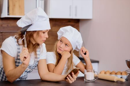 portrait of woman with kid girl thinking about baking something in kitchen, wearing aprons and caps for cooking