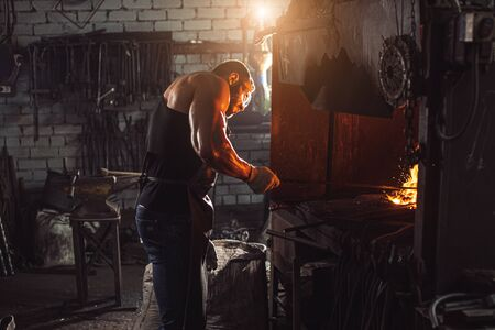 caucasian young strong blacksmith working with open fire in furnace. The blacksmith forging hot iron in workshop Standard-Bild