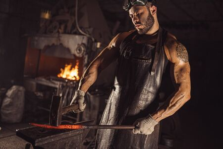 strong muscular brutal confident blacksmith man shaping red hot metal with hammer isolated in workshop, wearing leather apron, dark space Banco de Imagens
