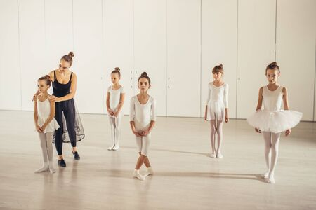 young caucasian ballerina in black suit teaching little children in white suits, practicing and coaching them in studio, correct body position