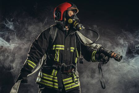brave firefighter extinguishing fire in smoke, using special equipment and wearing uniform and helmet