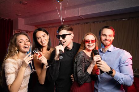young caucasian friends have fun together at karaoke bar, wearing dress and t-shirt, trendy modern clothes. indoors of karaoke room with neon lights
