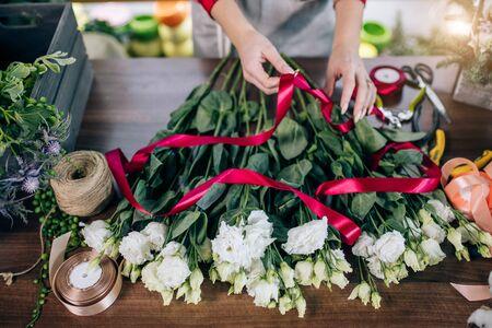 Draufsicht auf junge weibliche Hände, die Blumen in rotem Band binden und sie für den Verkauf vorbereiten, wundervoller schöner weißer Blumenstrauß auf dem Tisch. Blumenhändler