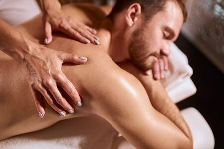 Delighted pleasant client with unshaven face, spending time in massage center, receiving hand massage from young masseur, closing eyes with relaxation