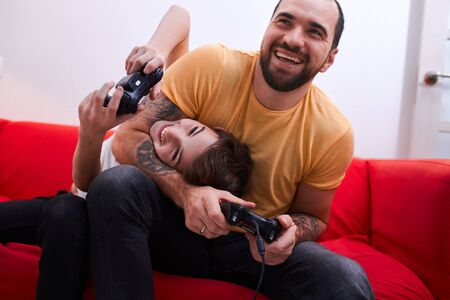 caucasian family, positive smiling man and happy kid boy sit on sofa and play video games together, holding joystick in hands Фото со стока
