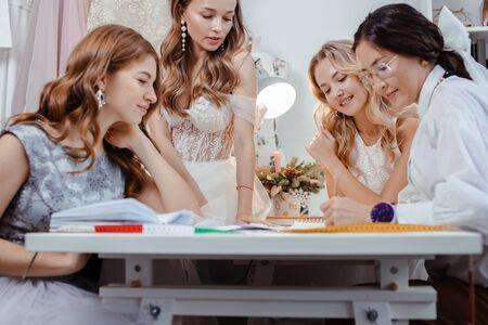 groupe de femmes caucasiennes réunies dans un bureau de créateurs pour discuter d'un nouveau style vestimentaire, de jeunes filles en robes de mariée blanches à la mode