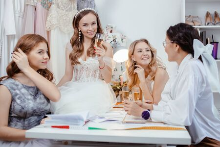 female tailor designer creating a new fashionable stylish wedding dress together with beautiful young caucasian girls models, attentively listen to her, write to notebook Standard-Bild