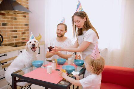 feliz, alegre, amistoso, familia caucásica celebrando cumpleaños junto con su animal doméstico, perro blanco, adorable mascota y sus dueños en casa. Aislado en cocina ligera Foto de archivo