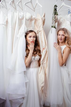 two young caucasian women in wedding salon, stay in shock among many dresses, going to get married