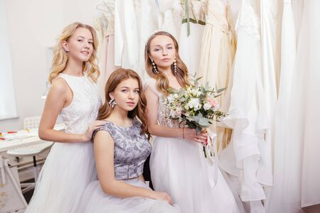 three young romantic ladies in wedding dresses, future brides, going to be married, posing together at camera among dresses, holding flowers in hands