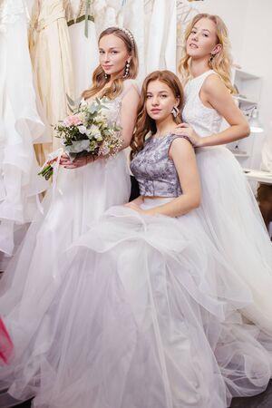 Porträt von gut aussehenden drei Frauen zusammen in Brautkleidern, posieren, zeigen neues Kleid von professionellen Designer-Schneidern, isoliert im Hochzeitssalon unter Kleidern Standard-Bild