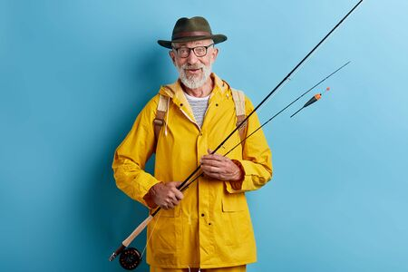 senior man preparing float to go fishing, close up photo. isolated yellow background, studio shot