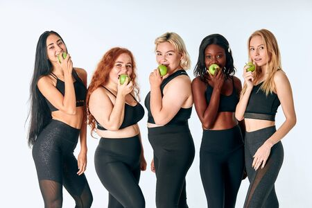 Young attractive girls eating green apple posing in studio, white background. Promotion of healthy lifestyle