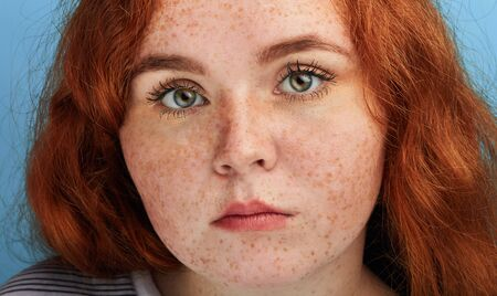 Close up shot of beautiful girl with ginger hair and freckles looking at the camera with serious expression, beauty , people, unusual beauty
