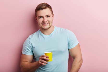 Happy smiling handsome young man in blue t-shirt drinking tea or coffee. close up portrait, isolated pink background, studio shot