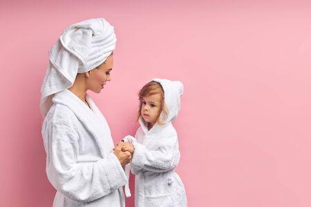 Nach dem Baden, Mutter und Tochter im Bademantel und Handtuch. Isolierter rosa Hintergrund Standard-Bild