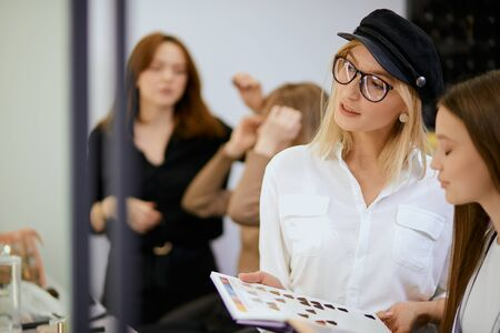 stylish modern blond hairdresser hold colour palette in hands and show, advice to young client which colour is appropriate for her face, isolated in beauty salon
