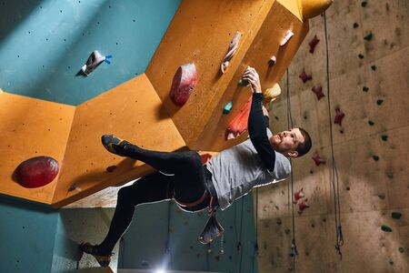 Flexible young physically challenged boulderer overhanging at large rock wall, rising up quickly, strong-willed and motivated person, overcomes life troubles and difficulties, inspiration concept.