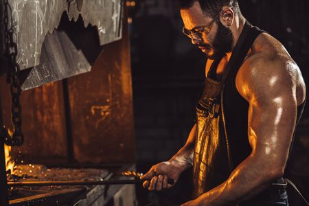 young caucasian strong man in black apron heating steel piece in furnace, powerful and strong muscles on hands, side view on caucasian man wearing gloves and eyeglasses for safety