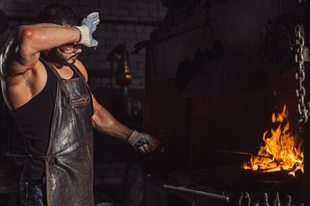 tired young caucasian blacksmith heating metal wearing brown leather apron and protective gloves, muscular hands, wipes sweat from face. power and strength Фото со стока