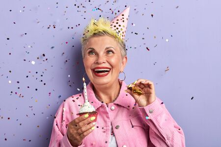 happy old woman looking at the flying confetti while holding cupcake, isolated over violet background Standard-Bild