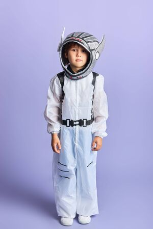 Spaceman concept. Portrait of little boy wearing helmet and white protective suit isolated over purple background