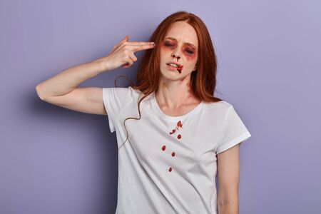 injured girl with closed eyes holding her hand, palm like a pistol near her temple, pretending killing herself, close up portrait, crime, studio shot.