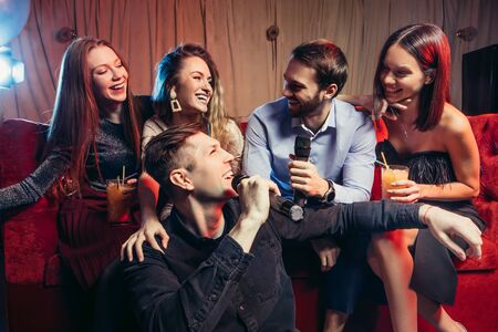 Photo of pretty girls and handsome guys singing in mic at party with friends, indoors of karaoke. party, celebration, entertainment concept Stock fotó