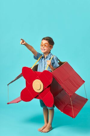 Portrait of excited boy inside of carboard box in form of airplane showing side, imagination of pilot. isolated blue background, sky