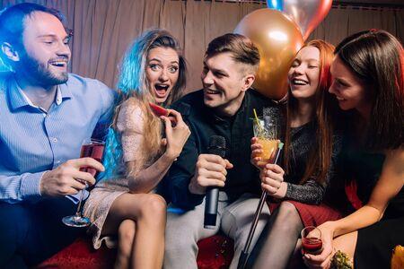 jóvenes felices y alegres y guapos tienen tiempo de fiesta en el bar de karaoke, vestidos con vestidos de fiesta y camisas. Vacaciones, celebración, concepto de fiesta Foto de archivo